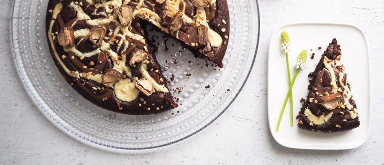 Maito- ja valkosuklaalla sekä hasselpähkinärouheella kuorrutettu suklaapiirakka valmistuu helposti Sunnuntai Mixin avulla.